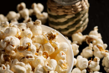 Popcorn in white ceramic bowl with salt shaker on a black wooden table.