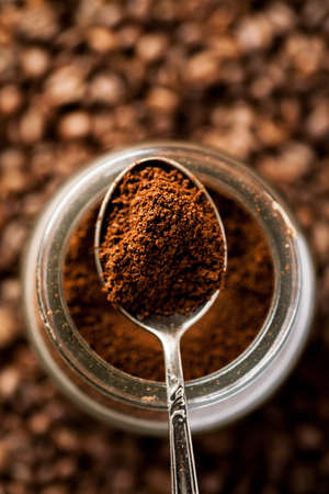 Ground coffee in silver spoon on a top of glass jar, shallow depth of field, vertical.