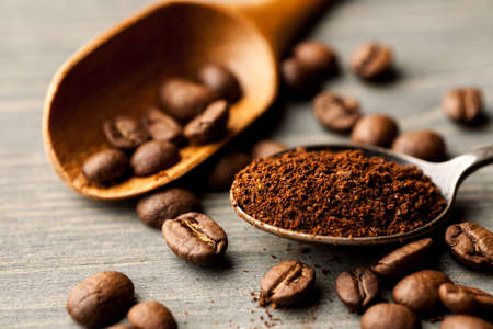 Coffee in a metal and wooden spoon closeup. Stock Photo