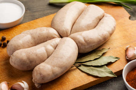 grille: Raw sausages for grille on a wooden board with spices ready for cooking.