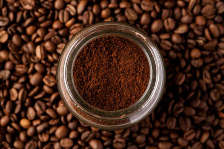Ground coffee in glass jar among coffee beans, top view.