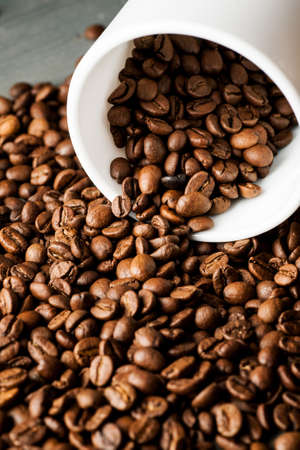 White ceramic mug with coffee beans on wooden table, vertical sot. Stock Photo