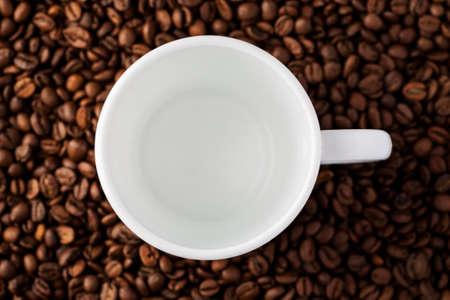 Empty white mug among coffee beans, top view.