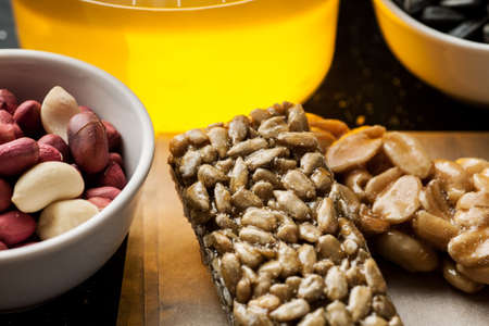 Peanut and sunflower seeds brittle with honey jar and raw ingredients in the white ceramic bowls.