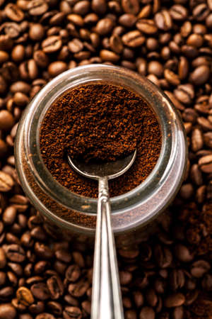 Silver spoon in glass jar full of ground coffee, vertical. Stock Photo