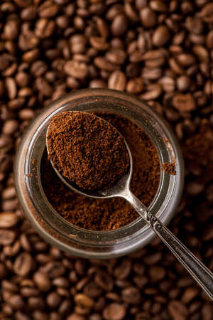 Ground coffee in a metal spoon on a top of glass jar, vertical shot.