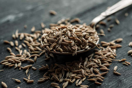 Cumin dry seeds in metal spoon on a black wooden table.
