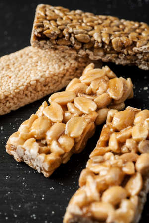 Peanut, sesame and sunflower seed brittle on a black wooden table, vertical.
