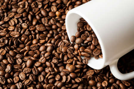White ceramic mug with coffee beans on wooden table. Stock Photo