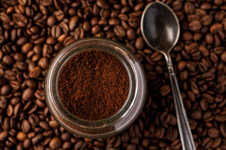 Ground coffee in a glass jar with coffee beans and metal spoon.
