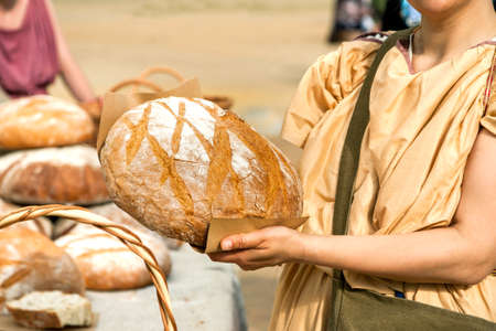 Bread seller woman holding big round loaf of bread in her arms.
