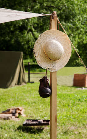 Straw hat and ceramic mug hanged on a wooden column, vertical Stock Photo