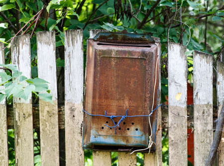 Old metal rusted mail box hanged on a wooden fence under green tree