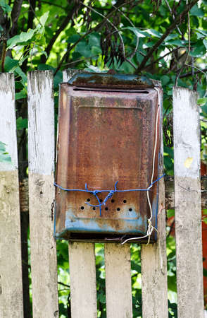 Old metal rusted mail box hanged on a wooden fence under green tree, vertical