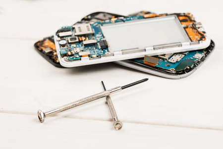 Disassembled cell phones and other gadgets in repair shop