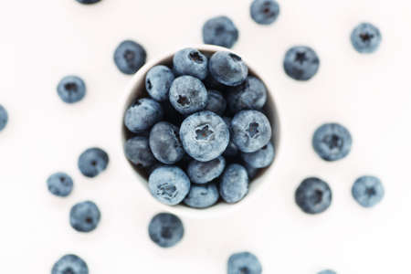 Heap of fresh ripe blueberries in a white ceramic bowl on a white background, top view, shallow depth of field