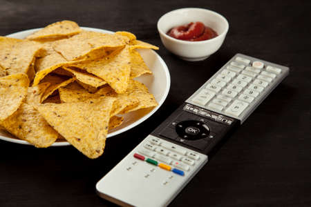 Nachos chips with sauce and TV remote on a black table Imagens
