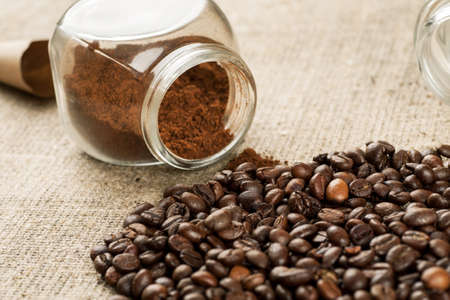Roasted coffee beans and glass jar with ground coffee inside