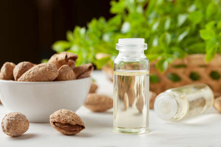 Small glass bottle with oil inside and almond in shell near on a white table with greenery in wicker basket behind Stock Photo