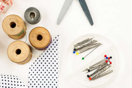 Set of tools and accessories for sewing and needlework with threads in spools, needles, measuring tape and other items on a white background, top view Stock Photo