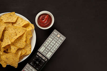 Nachos chips with sauce and TV remote on a black table, top view