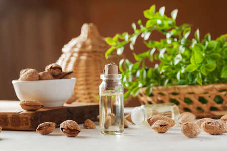 Small glass vial with paper cork and oil inside, almond in shell and basket with greenery on a white table