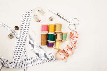 Set of tools and accessories for sewing and needlework with threads in spools, needles, measuring tape and other items on a white background, top view 스톡 콘텐츠