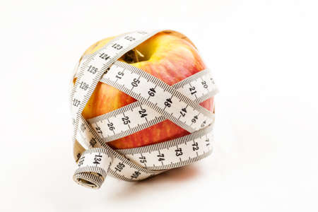 Ripe red juicy apple with measuring tape around it on a white background Standard-Bild