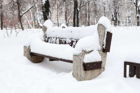 Snow covered bench among snowbanks in city park