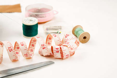 Set of tools and accessories for sewing and needlework with threads in spools, needles, measuring tape and other items on a white background