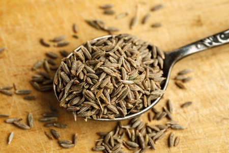Cumin seeds in metal spoon on a wooden table, top view