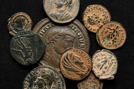 Pile of ancient coins on black background