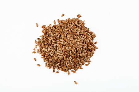 Pile of flax seeds on a white background