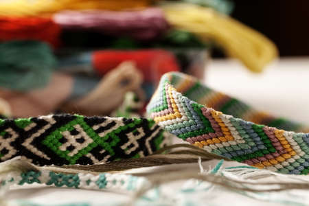 Bright friendship bracelets on a white table with heap of colored threads