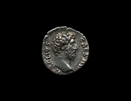 Ancient roman silver coin with portrait on it isolated on black