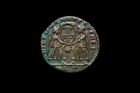 Ancient roman coin isolated on black 写真素材