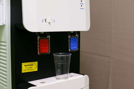 Office electric water cooler with empty plastic cup 写真素材