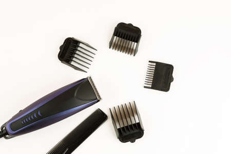 Electric hair clipper with different size attachments on a white background, top view