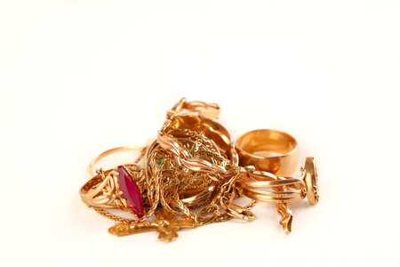 Pile of gold jewellery on a white background