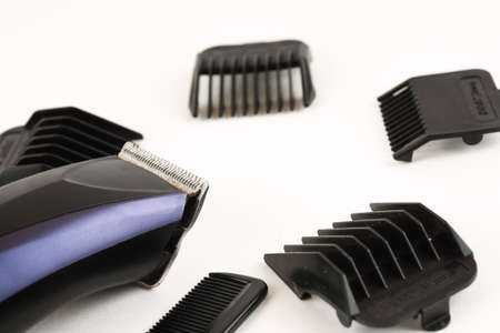 Electric hair clipper with different size attachments on a white background
