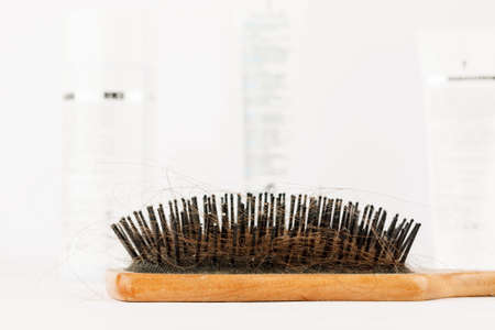 Comb with loose hair in it on a white table. closeup shot 写真素材