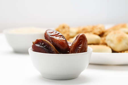 Dried dates in white ceramic bowl with traditional oriental cookies in the background, close-up shot