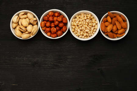 Different nuts in ceramic bowls on a black wooden table, top viev, text space