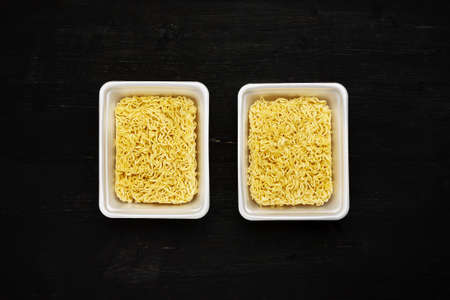 Two boxes of instant noodles in containers on a black wooden table, top view