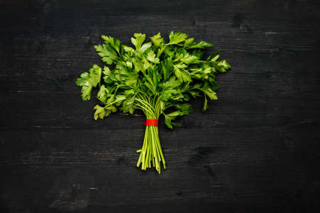 Bunch of green fresh parsley on a black wooden table, top view