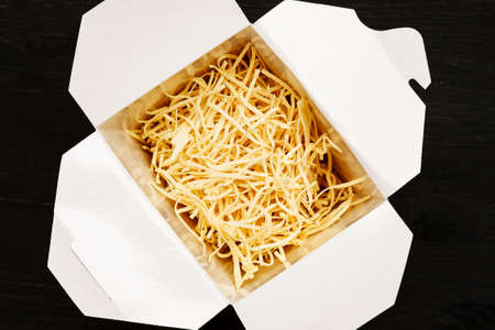 Dry noodles in paper box on a black table, top view