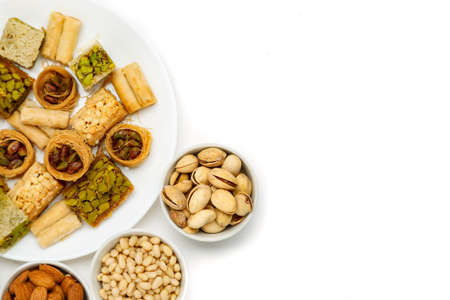 Dolci orientali tradizionali in piatto bianco con noci diverse su un tavolo bianco, vista dall'alto, spazio copia