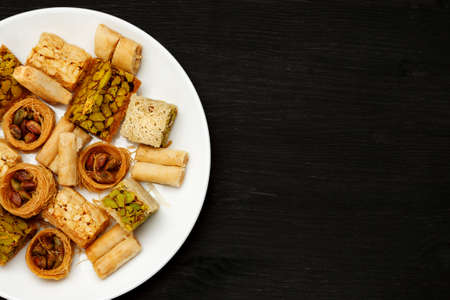 Traditional oriental sweets in white plate with different nuts on a black table, top view, copy space 写真素材