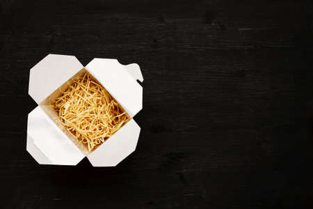 Dry noodles in paper box on a black table, top view, text space