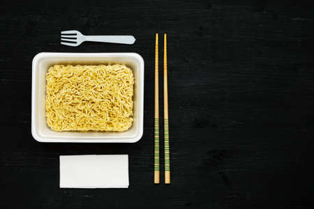 Instant noodles in container with plastic fork, chopsticks and napkin on a black wooden table, top view, copy space